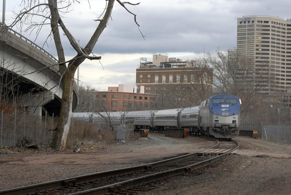 An Amtrak train pass north of Broad Street in Hartford on its way to Union Station, which will be the final stop in the new busway. Space to the left of the track will be cleared to allow for north and south bound lanes for the busway.
