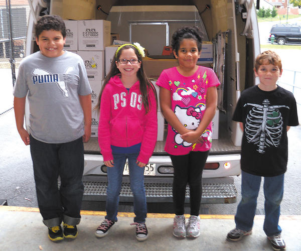 Maugansville Elementary students Milben Obando, Morgan Rettig, Aamani Horner and Dakodah Smith assist with the loading of food for Maryland Food Bank - Western Branch.