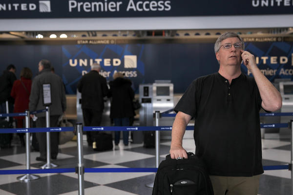 A United Airlines passenger looks at the flight information board at O'Hare International Airport.