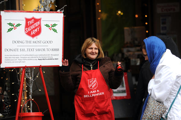 Melissa Santiago works the Salvation Army collection stand in downtown Bethlehem on Friday.