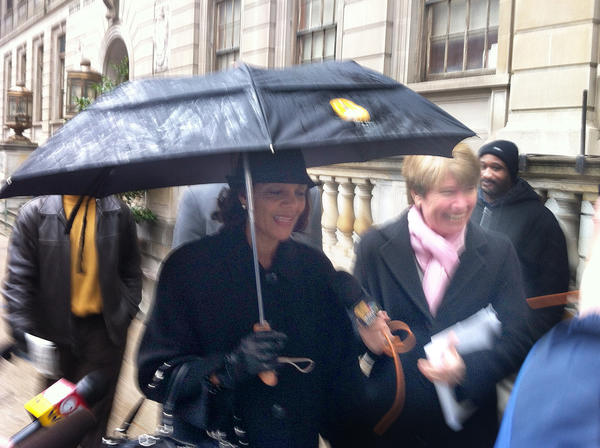 Former Baltimore mayor Sheila Dixon (under umbrella) leaves court after a probation hearing.