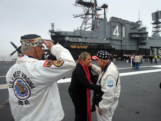 Pearl Harbor survivor Stu Hedley, 91, left, salutes, as Doyle McKee is thanked for his service by Rebecca Shaffner during the annual Pearl Harbor Day Remembrance Ceremony aboard the USS Midway Museum's flight deck in San Diego.
