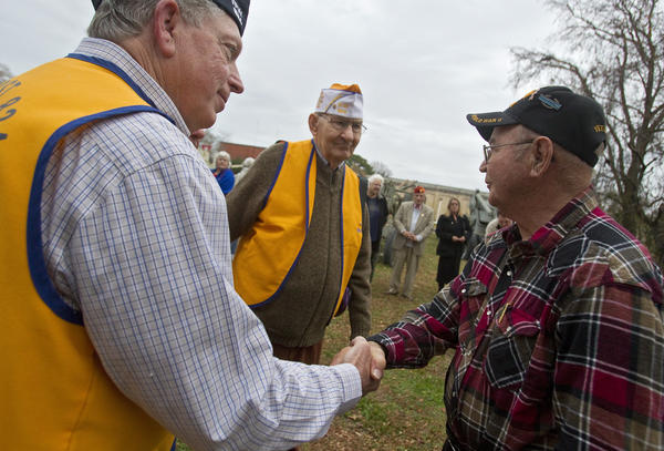 Veteran Tom Kolcum (right) shakes hands with World War II veteran Ken Bernstrom following a service held Friday at the Virginia War Museum to honor the seventy-first anniversary of the attack on Pearl Harbor.