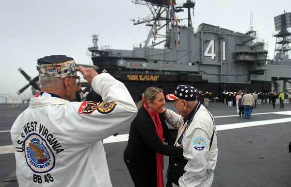 Pearl Harbor survivors Stu Hedley, 91, left, salutes, as Doyle McKee is thanked for his service by Rebecca Shaffner during the annual Pearl Harbor Day Remembrance Ceremony aboard the USS Midway Museum's Flight Deck in San Diego, Friday Dec. 7, 2012. The ceremony was free for the general public and was co-hosted by the Pearl Harbor Survivors Association and the USS Midway Museum. The Californian tall ship from the Maritime Museum of San Diego fired a one-gun salute off the Midway's bow and a wreath was tossed overboard to those who sacrificed and those who survived on December 7, 1941.