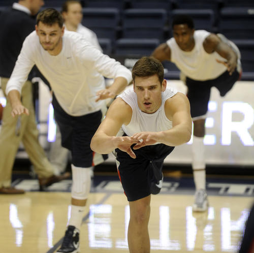 UConn's Tyler Olander, center, goes through some drills before facing Harvard at Gampel Pavilion Friday night.