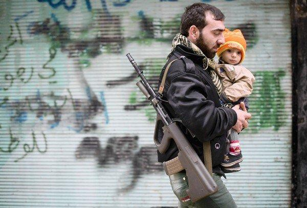 A rebel fighter with his son after Friday prayers in Aleppo, Syria. As rebels have scored major gains, U.S. officials have begun weighing whether to give them military assistance.