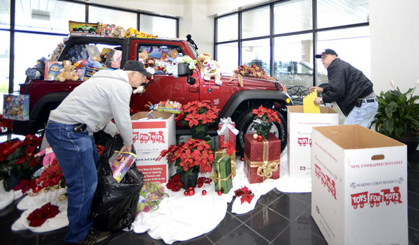 Volunteers Tom Bisesi, left, and Jeff Latta pack up toys donated at Hoffman Jeep on Friday morning as part of the annual U.S. Marine Corps Toys for Tots program.  They are collecting until Dec. 18.