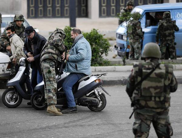 Lebanese soldiers search civilians at a checkpoint in Tripoli. The city has taken on the appearance of a war zone, a kind of mirror image of strife-torn neighboring Syria.
