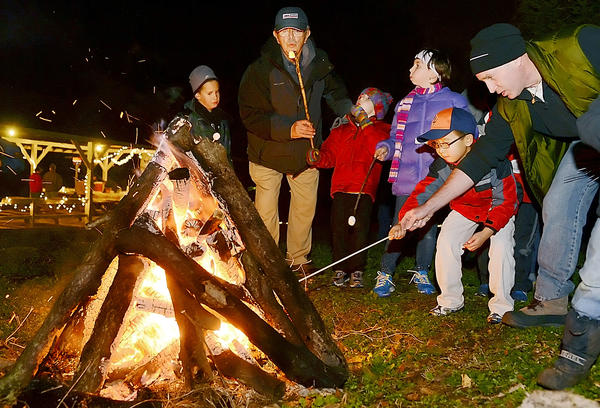 "People of all ages roast marshmallows at a bonfire in Funkstown Community Park Friday night as part of Funkstown""s Old Tyme Christmas."