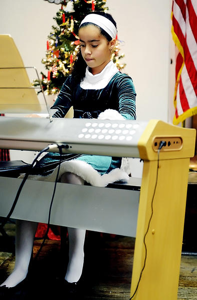 "Mikala Cunningham, 10, plays ""Carole of the Bells"" on the piano at Town Hall in Funkstown Friday night as part of Funkstown""s Old Tyme Christmas."