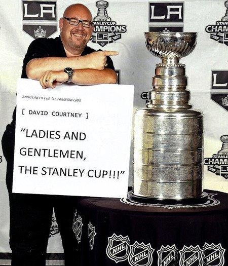 David Courtney, who began working for the Kings as an intern in 1971, fulfills a lifetime dream of posing with the NHL trophy that team won for the first time last season.