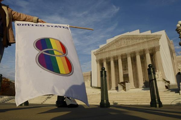 A supporter of same-sex marriage holds a flag that depicts two wedding bands outside the Supreme Court in Washington on Nov. 30.