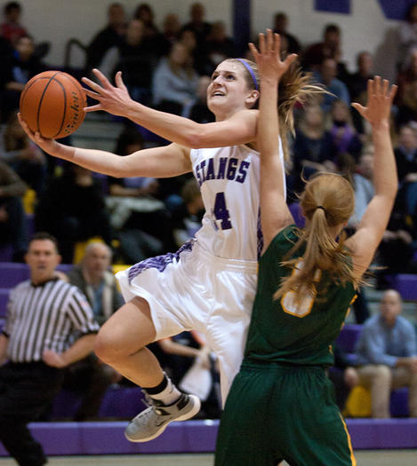 Alexis Glasgow of Rolling Meadows goes for a layup against Elk Grove's Kelly Naughton.