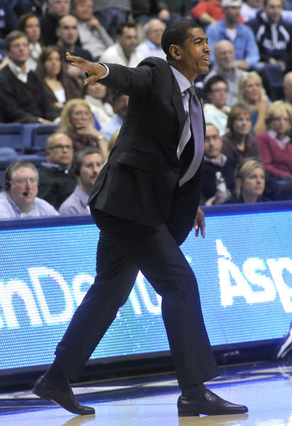 UConn coach Kevin Ollie barks orders to his team against Harvard at Gampel Pavilion Friday night.