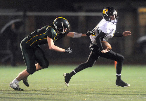 Central Catholic's Jeffrey Gulyas (left) sacks Archbishop Wood's QB Tom Garlick (right) during the semifinal round of the PIAA 3A football tournament Friday night.