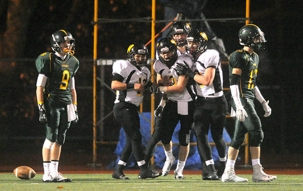 Archbishop Wood's Chris Rahill (center) gets mobbed by his teammates after catching a 53 yard touchdown pass to make the stretch the lead to 27 - 0 over Central Catholic High School in the semifinal round of the PIAA 3A football tournament Friday night.