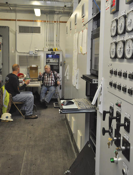 Kevin Hundstad, NorthWestern Energy electrical generation plant operator, left, and Kenneth M. Nagy, manager of NRG 4U Consulting, LLC, of Tolland, Conn., talk near a control panel at the plant south of Aberdeen Friday. American News Photo by Anita Meyer