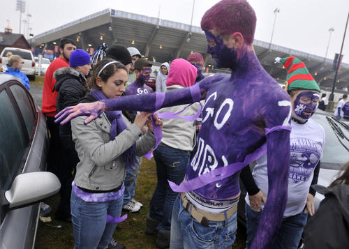 North Branford seniors Rachel Boyers adds streamers to the arms of Kevin Juhasz before their team takes on Ansonia in the Class S state football championship at Rentschler Field Saturday.