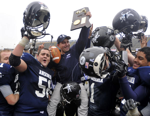 Ansonia players hoist head coach Tom Brockett, center, up after defeating North Branford in the Class S state football championship at Rentschler Field Saturday.