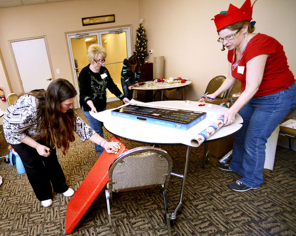 Parent and recipient Sharleen Bowers, left, puts a bow on her wrapped toy while Santa's helpers Kelly Peacock, center, and JoAnn Wright, right, wrap some of her other toys at the Toy Giveaway held at 365 Church in Martinsburg Saturday.