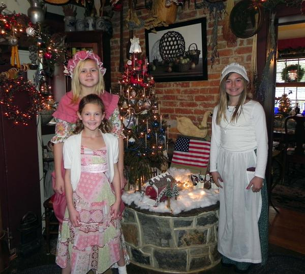 Barbara and Dick McCracken's granddaughters Paige Myers, 13, Aspen Buffington, 9, and Skylar Lambert, 11, stand in the kitchen of the McCracken House near the well and the red/white/blue Christmas tree.