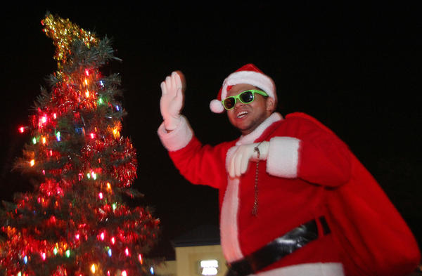 Dressed as Santa, Patrick Mendez, 19 waves aboard the Langley Air Force Base Chapel float at the Hampton Holly Days parade on Saturday evening in downtown Hampton.