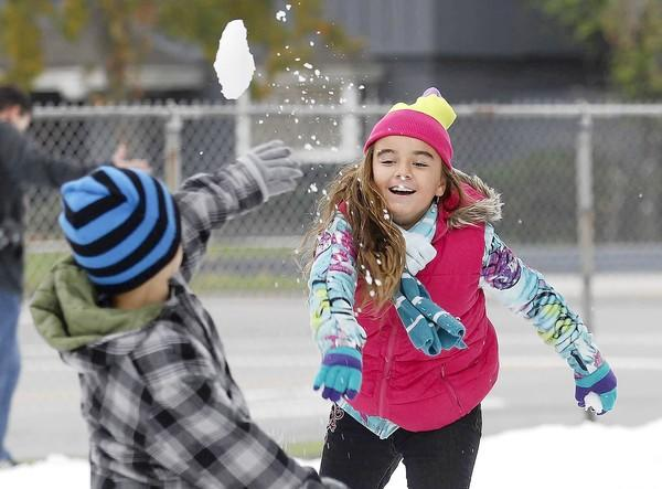 Hailey Garcia, 9, right, of Huntington Beach, throws a snowball at her brother Caleb, 8, during the Holiday Snow Land event at Balearic Community Center in Costa Mesa on Saturday.