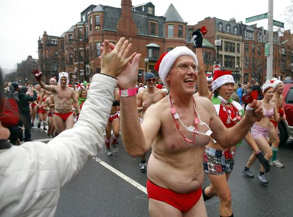 "A participant in the annual ""Santa Speedo Run,"" a charity race through the streets of the Back Bay neighborhood of Boston, Massachusetts, gets a high five from the crowd lining the street."