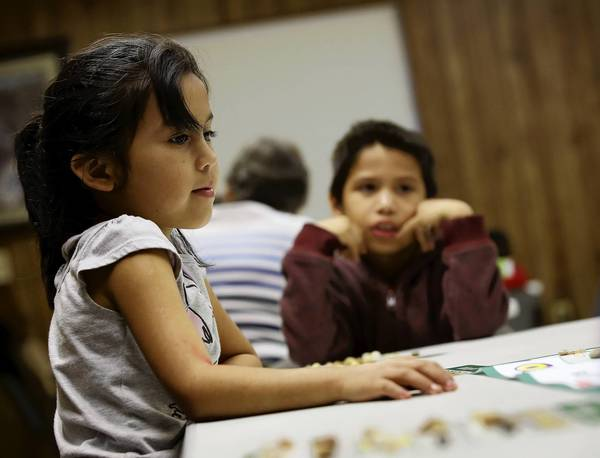 Litzy Cabrera and brother Arnulfo play a game of bingo at the Great Kids Explorer Club in DeLeon Springs recently. (Jacob Langston/Orlando Sentinel)