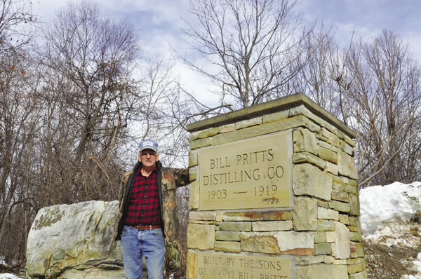 "H. Dale Pritts at the former distillery site of his great-grandfather, ""Old Bill"" Pritts. Today, the site is home to a monument recognizing his days as a legitimate moonshiner."