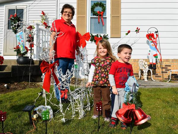 On The Cheap tipster Joann Dove and her twin grandchildren, Carly and Carson Mulhern, age 3, stand in her Salisbury Township yard by Christmas decorations made of tomato plant cages.
