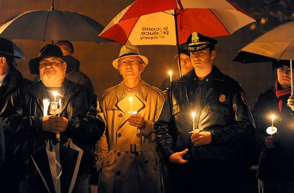 Police Chief Jason Schiffer (right) joined the South Side community in a candle-light vigil against violence on Third Street Friday night.