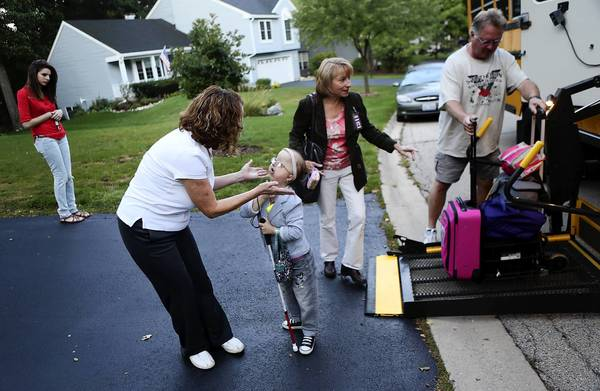 Mary Kish bends down to give her daughter, Michelle Kish, 15, a kiss before she gets on the bus in August for her first day of high school outside their home in Bartlett. Michelle's medical equipment is being loaded at right. Her sister, Sarah, 17, looks on at left. Michelle's full-time day nurse Jane Swanson, in dark jacket, walks toward the bus.