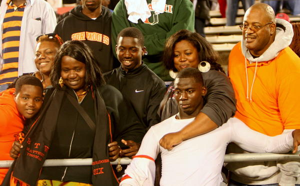 Miami Booker T. Washington star linebacker Matthew Thomas poses with family and friends, including his mother Mariska Nyon (with scarf) and father Billy Thomas (far right, orange hoodie) after the Tornadoes won the Florida Class 4A state football championship. It was the first time Mariska had ever seen her son play live.