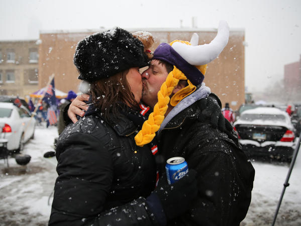 Bears fan Stacey Manley gets a kiss from Vikings fan Tom Look, a total stranger, while tailgating in a parking lot.