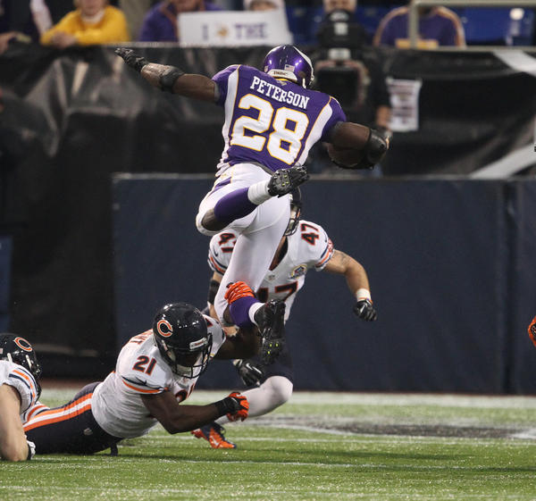 Vikings running back Adrian Peterson leaps over Major Wright for some yardage during the first half.