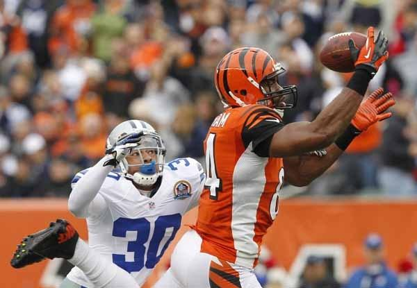 Cincinnati Bengals tight end Gresham makes catch under pressure from Dallas Cowboys' Moore defense during first half of play in their NFL football game in Cincinnati.