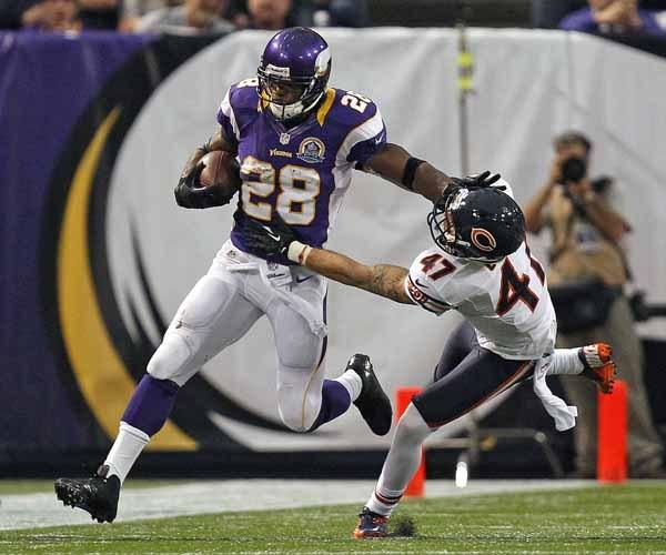Minnesota Vikings running back Adrian Peterson pushes off of Chicago Bears safety Chris Conte.