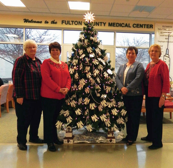Fulton County Medical Center Auxiliary officers, from left, Carol Mellott, treasurer; Nancy Younker, secretary; Judy Eisaman, vice president; and Sally Cover, president, pose around the Tree of Love following Sunday's ceremony at the medical center in McConnellsburg, Pa.