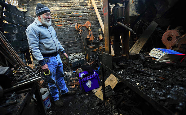 Shepherdstown metal artist Dan Tokar looks over fire scene Thursday in Shepherdstown, W.Va., for materials he can reclaim for use. He intends to continue his craft.