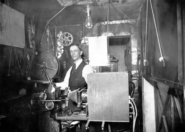 Unidentified projectionist in the projection booth at the Stockton Theatre in Stockton, Calif., 1912. A paper calendar on the wall is open to the first week of July 1912.""
