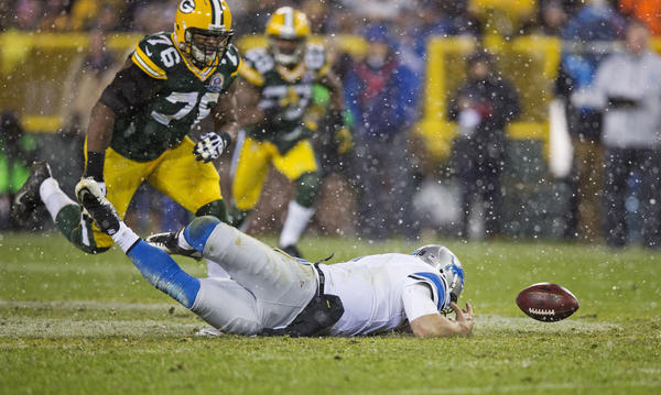 Matthew Stafford #9 of the Detroit Lions dives for the ball he fumbled as Mike Daniels #76 of the Green Bay Packers closes in at Lambeau Field on December 9, 2012 in Green Bay, Wisconsin. Green Bay won 27–20.