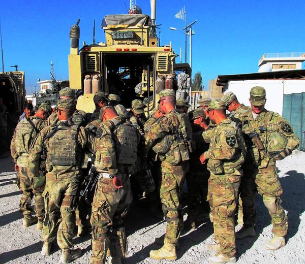 U.S. troops say a prayer for protection behind their armored vehicles before setting out on patrol, a daily ritual, in Kandahar, Afghanistan.