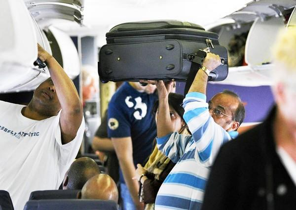 Airline workers say overhead space complaints is one of passengers' most annoying habits.