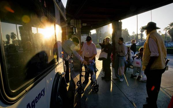 A woman steps off a Riverside Transit Agency bus with a little bit of help. Nationally, trips on public buses and trains rose 2.6% in the first three quarters of 2012, a new report says.