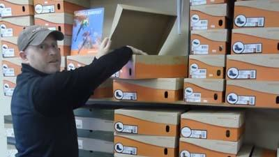 Owner Bob South stocks new shoe inventory at No Boundaries in Boyne City.