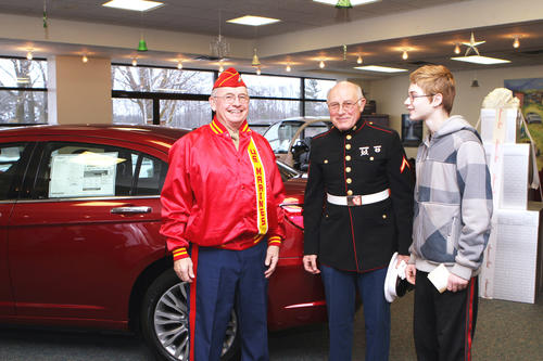 M. CHRIS LEESE/NEWS-REVIEW Capt. Ray Fisher of East Jordan, (from left) Pfc. Paul Michael of East Jordan both representing Northern Michigan Detachment Marine Corps League and Jesse Peters, 14 of East Jordan all volunteer to help Saturday with the annual Toys for Tots open house at Fox Motors of Charlevoix.