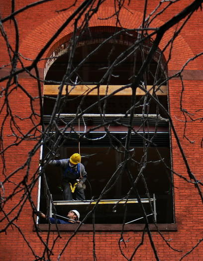 In 2007, workers restore a window at 300 Cathedral St., which is now being converted to apartments by a Washington-based developer.