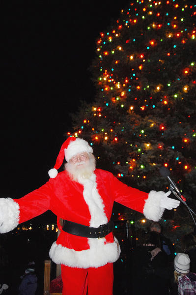Santa Claus gestures to the crowd as he lights the Petoskey Christmas tree on live television, Friday evening, at the Petoskey Downtown Holiday Open House.