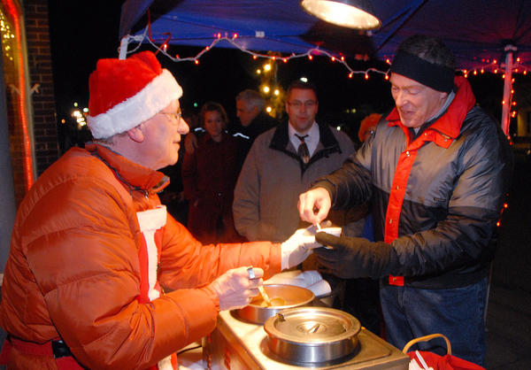 Tom Sheffler, (left) of Julienne Tomatoes, serves a cup of tomato basil soup to Jerry Messinger, of Petoskey. The downtown eatery served approximately 20 gallons of soup to the community. Most downtown businesses served holiday treats to the many hundreds who spent the evening browsing the town.
